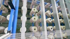 Большие катушкы свертывают спиралью волокно на шкафе завода сток-видео