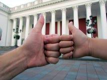 Большие пальцы руки вверх на небольшом и сильной руке стоковые изображения
