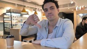 Большие пальцы руки вниз молодым человеком в кафе