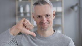 Большие пальцы руки вниз серым человеком волос на работе, смотря камеру