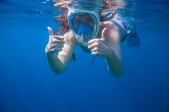 Большие пальцы руки девушки подводные показывая Snorkeling лицевой щиток гермошлема женщины полностью Стоковая Фотография