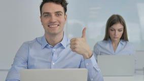 Большие пальцы руки поднимают молодым бизнесменом в офисе акции видеоматериалы