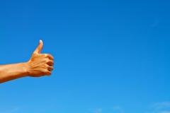 Большие пальцы руки поднимают символ против голубого неба Стоковое фото RF