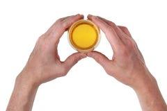 Большие руки ` s человека держат малое стекло с пивом Стоковые Изображения