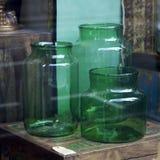 Большие стеклянные зеленые чонсервные банкы которые можно использовать как вазы показаны в окне магазина Стоковое Изображение RF
