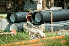 Большие черные и оранжевые пластичные трубы дренажа водоснабжения или канализации подготовили для реконструкции трубопровода в ра Стоковые Изображения
