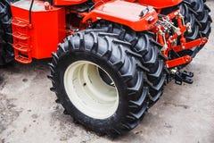 Большие черные колеса резиновой автошины современных красных трактора или зернокомбайна или жатки Стоковые Фотографии RF