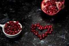 Большинств seducive плод на день Святого Валентина - гранатовое дерево уговаривать, красные семена аранжировало в форме сердца стоковое изображение