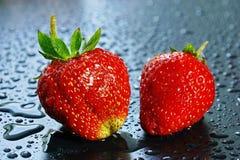 2 больших зрелых красных ягоды клубники на темной предпосылке мочат Стоковые Изображения RF