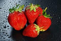 5 больших зрелых красных ягод клубники на темном wate предпосылки Стоковые Фотографии RF