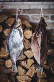 2 больших копченых рыбы висят на предпосылке штабелированного швырка Стоковое Фото