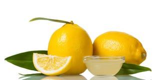 2 больших лимона с листьями, лимонным соком в малом шаре изолированном на белизне Стоковые Изображения RF