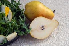 2 больших сладких груши около черной плиты Легкий вкусный салат лета с грушей, arugula, сыром бри, гайками сосны, соусом меда _ стоковые изображения rf