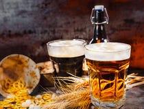 2 больших стекла с свеже политым темным и светлым пивом около whe Стоковые Изображения RF