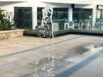 Большое влажное, красивое, прозрачное падение летая воды брызнутое в воздухе против фона открытого кафа стоковое фото