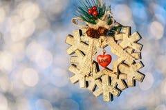 Большое деревянное украшение рождества хлопь снега на предпосылке bokeh Стоковая Фотография