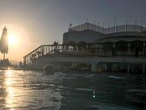 Большое каменное здание с пешеходным мостом с сводами над бассейном около воды, бассейном против голубого неба и большим солнцем стоковое фото rf