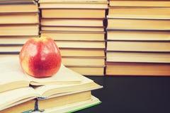 Большое красное яблоко и много книг стоковое изображение rf