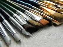 Большое разнообразие щеток, инструментов для красить и скульптуры на linen предпосылке ткани Стоковое Фото