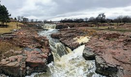 Большое река Сиу пропускает над утесами в Sioux Falls Южной Дакоте с взглядами живой природы, руинами, путями парка, мостом следа стоковое фото