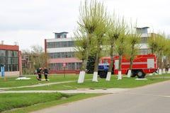 Большое спасательное средство красного огня, тележка для того чтобы потушить огонь и пожарные мужчины подготовлены для работы на  Стоковая Фотография