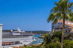 Большое туристическое судно стоит в порте Менорки рядом с яхтами и пальмами, очень близко к улицам города, Испания Стоковое фото RF