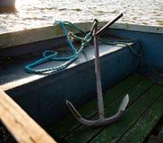Большой анкер металла сидит внутри небольшой голубой весельной лодки Принятый во время предыдущего захода солнца на небольшом озе стоковые изображения rf