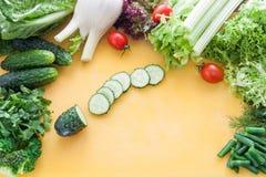 Большой ассортимент зеленых цветов, салата и овощей на желтой доске с отрезанным огурцом в разбивочном взгляд сверху стоковые изображения rf
