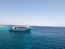 Большой белый корабль, шлюпка, вкладыш круиза туристский на голубом лазурном море, океане с рифами против голубого неба стоковая фотография
