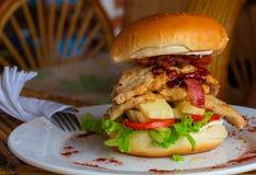 Большой бургер на плите Жалуйтесь бургер с сыром, ветчиной и томатом на белой плите Стоковое Изображение RF