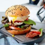 Большой бургер с котлетой, овощами, яичком и свежим креном Сандвич для фаст-фуда завтрака Еда ` s людей Стоковые Фотографии RF