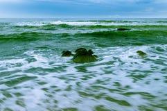 Большой валун в океане сизоватого зеленого цвета стоковые изображения rf