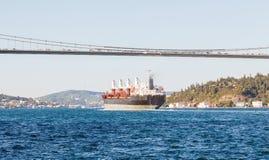 Большой грузовой корабль продолжая вдоль канала Bosphorus на предпосылку моста на предпосылке Стоковое Изображение RF