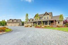 Большой деревенский дом фермы с подъездной дорогой гравия и зеленым ландшафтом. стоковая фотография