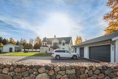 Большой дом семьи с двойными гаражом и автомобилем размера припарковал в фронте Жилой дом с конкретной входной дверью подъездной  Стоковые Изображения