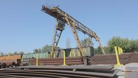 Большой желтый кран на козлах двигает вокруг склада с металлом, крана на козлах против голубого неба