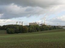 Большой завод среди леса и зеленых полей стоковое изображение rf