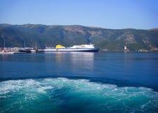 Большой корабль транспорта поставленный на якорь в доке с зелеными холмами в предпосылке Стоковые Изображения