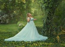 Большой, красивый, молодая женщина в роскошном голубом платье с длинным поездом идет в зацветая сад Модель стоковое изображение