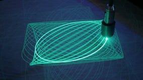 Большой маятник рисует многоточия с светом на поверхности фосфора акции видеоматериалы