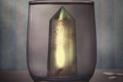 Большой мистический граненный кристалл кварца в стекле очищенной воды на абстрактном конце-вверх предпосылки Стоковые Изображения RF