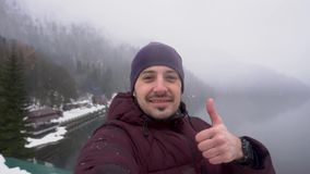 Большой палец руки показа человека вверх на озере Ritsa в абхазии в зиме видеоматериал