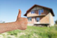 Большой палец руки показа человека до дома в предпосылке стоковые фото