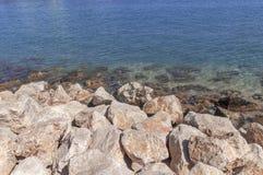 Большой передний план камня моря и голубой предпосылки моря на Греции Стоковые Изображения