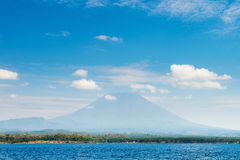 Большой подъем вулкана над островом и морем Стоковые Фото