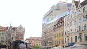 Большой пузырь мыла летает в воздух на фестивале города против фона городской архитектуры