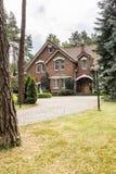 Большой разделенный экстерьер дома с кирпичными стенами и красным behi крыши стоковое изображение