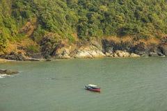 большой розовый прогулочный катер на воде в заливе моря на предпосылке наклона горы с зеленым лесом и утесами стоковая фотография