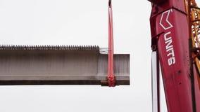 Большой серый конкретный луч быть осторожным поднят красным краном на районе конструкции видеоматериал