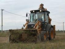 Большой сильный трактор извлекает землю работает на строительной площадке стоковые изображения rf